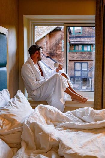 Full length of man wearing robe holding coffee cup sitting at window