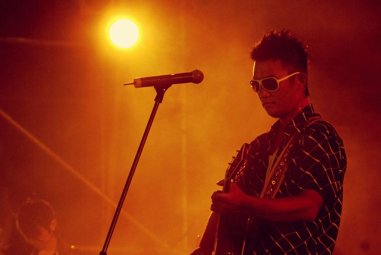 Young man playing guitar at music concert