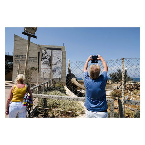 Rear view of man photographing woman against clear sky