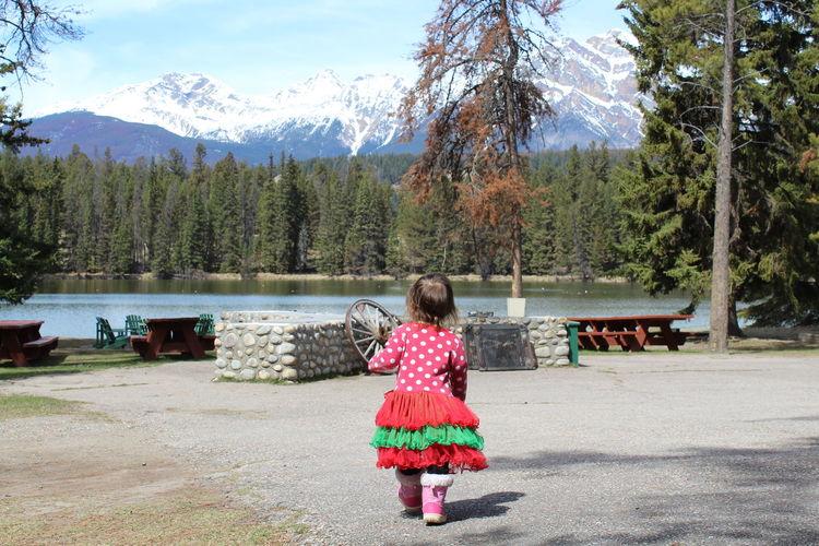 Rear view of baby girl walking on road towards lake