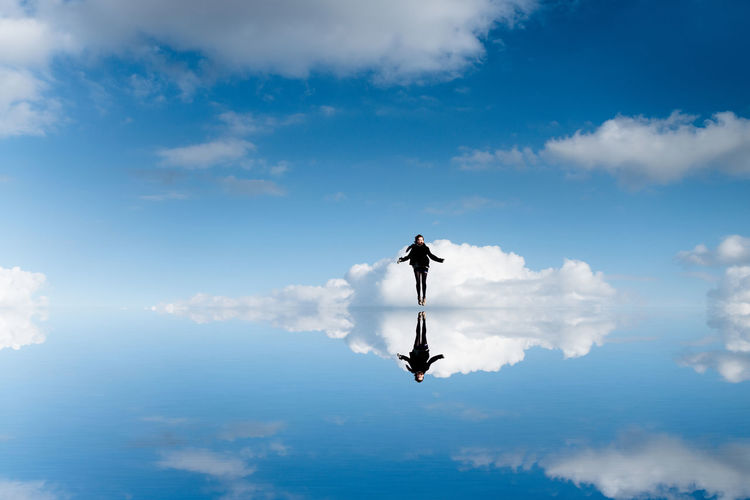Digital Composite Image Of Young Woman Levitating Over Calm Lake In Blue Sky