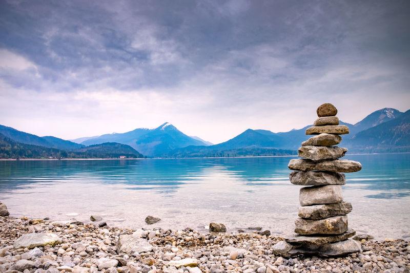 Pile stones on beach. rock heap of gray dolomite pebbles close to alpine lake, mountains silhouettes
