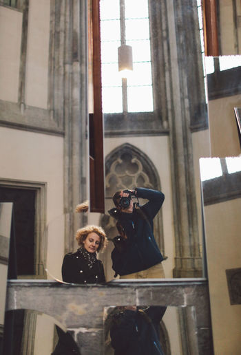 Man photographing himself and woman in a mirror