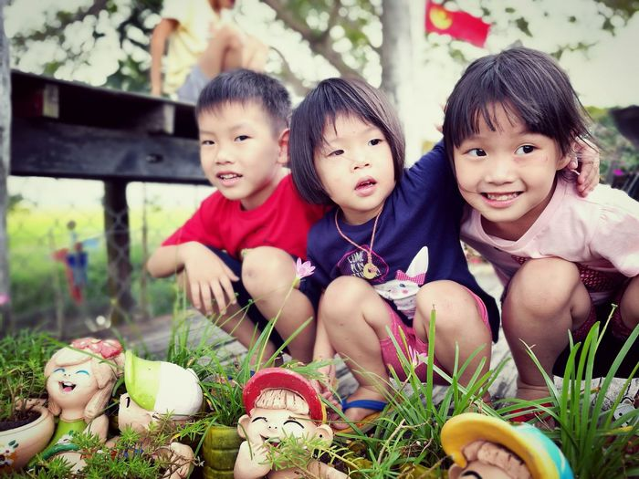 Siblings crouching by figurines at park