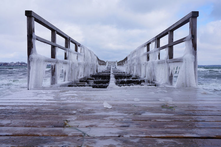 Frozen Pier with icicles Blue Cold Temperature Looking At Camera Bizarre Baltic Sea Water Frozen Winter Pier Icicles Weather Phenomenon Weather Climate
