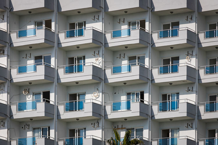 A white residential building with flat, identical balconies with ripped air conditioners