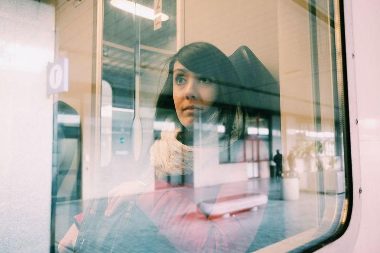 Thoughtful Woman Traveling In Train Seen Through Window