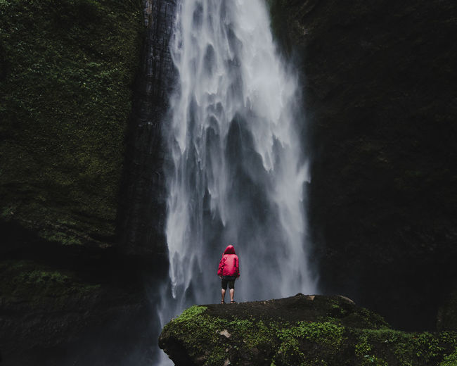 Rear view of woman standing against waterfall