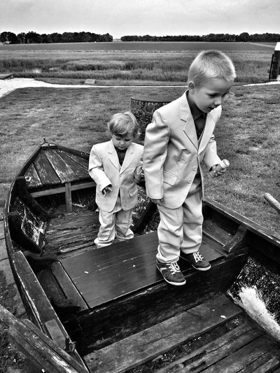 Cute boys in full suits standing on moored boat at field