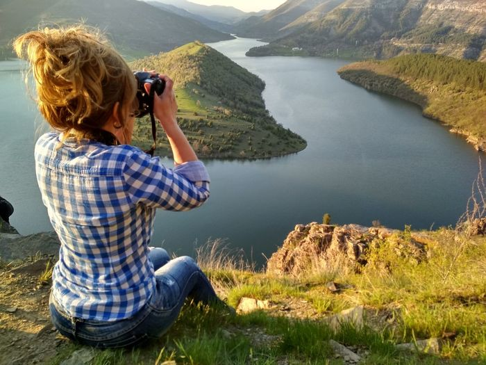 Rear View Of Mature Woman Photographing Lake While Sitting On Mountain