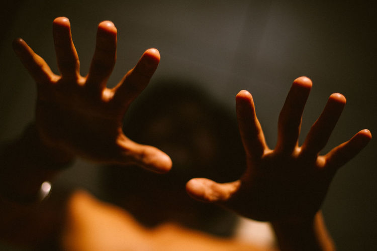 Close-up of silhouette hands against blurred background