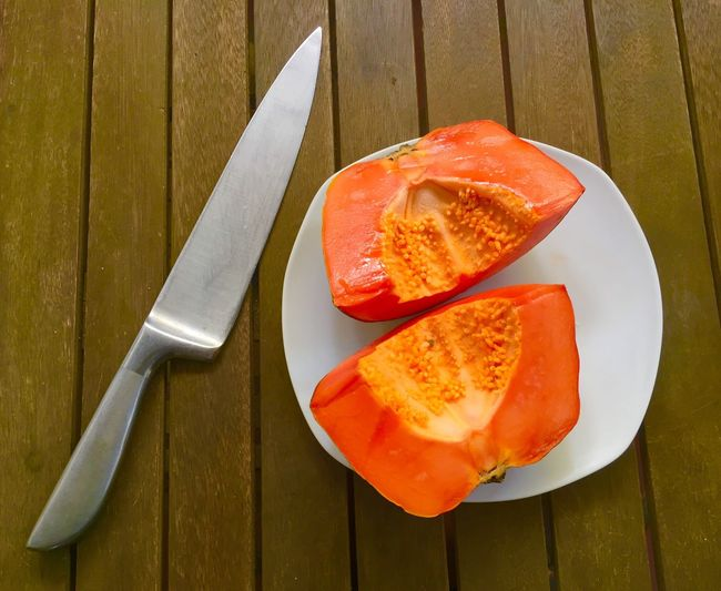 Papaya cut in two pieces with knife Papaya Food Food And Drink High Angle View No People Healthy Eating Freshness Plate SLICE Fruit Ready-to-eat Close-up