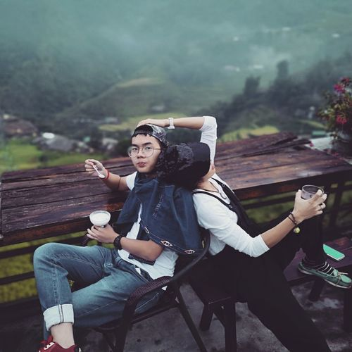 Full length of young couple sitting on seat