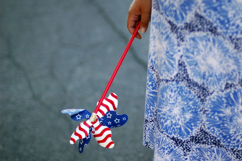 Midsection of woman holding american flag pinwheel