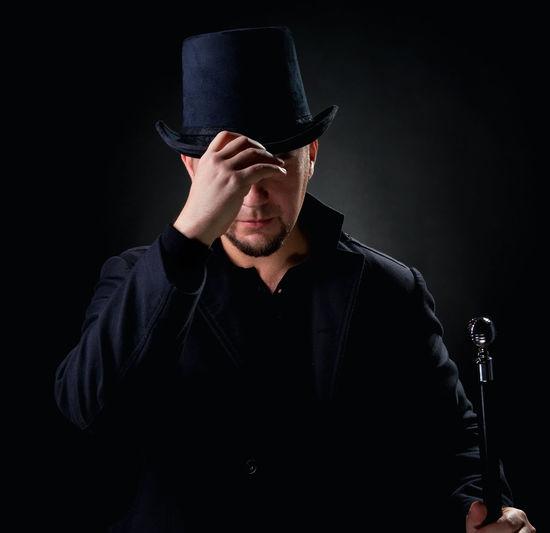 Man Wearing Hat Against Black Background