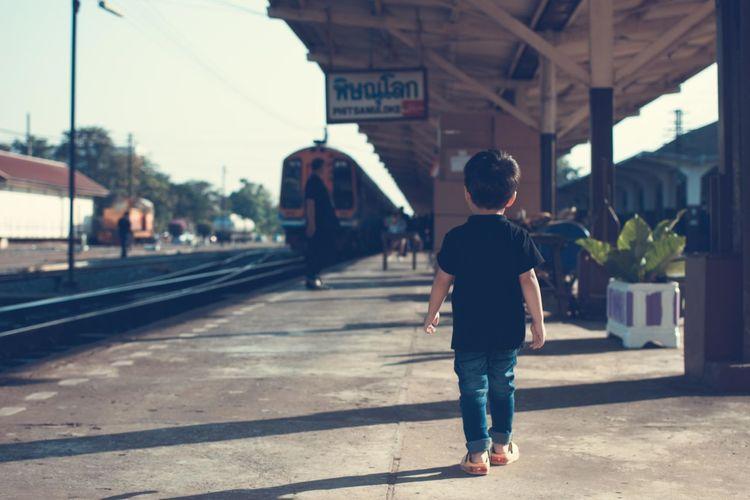 Full length rear view of boy walking at railroad station platform