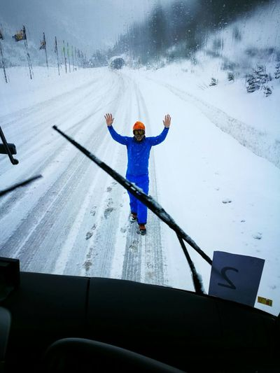 Man with arms raised standing against bus during winter seen through windshield