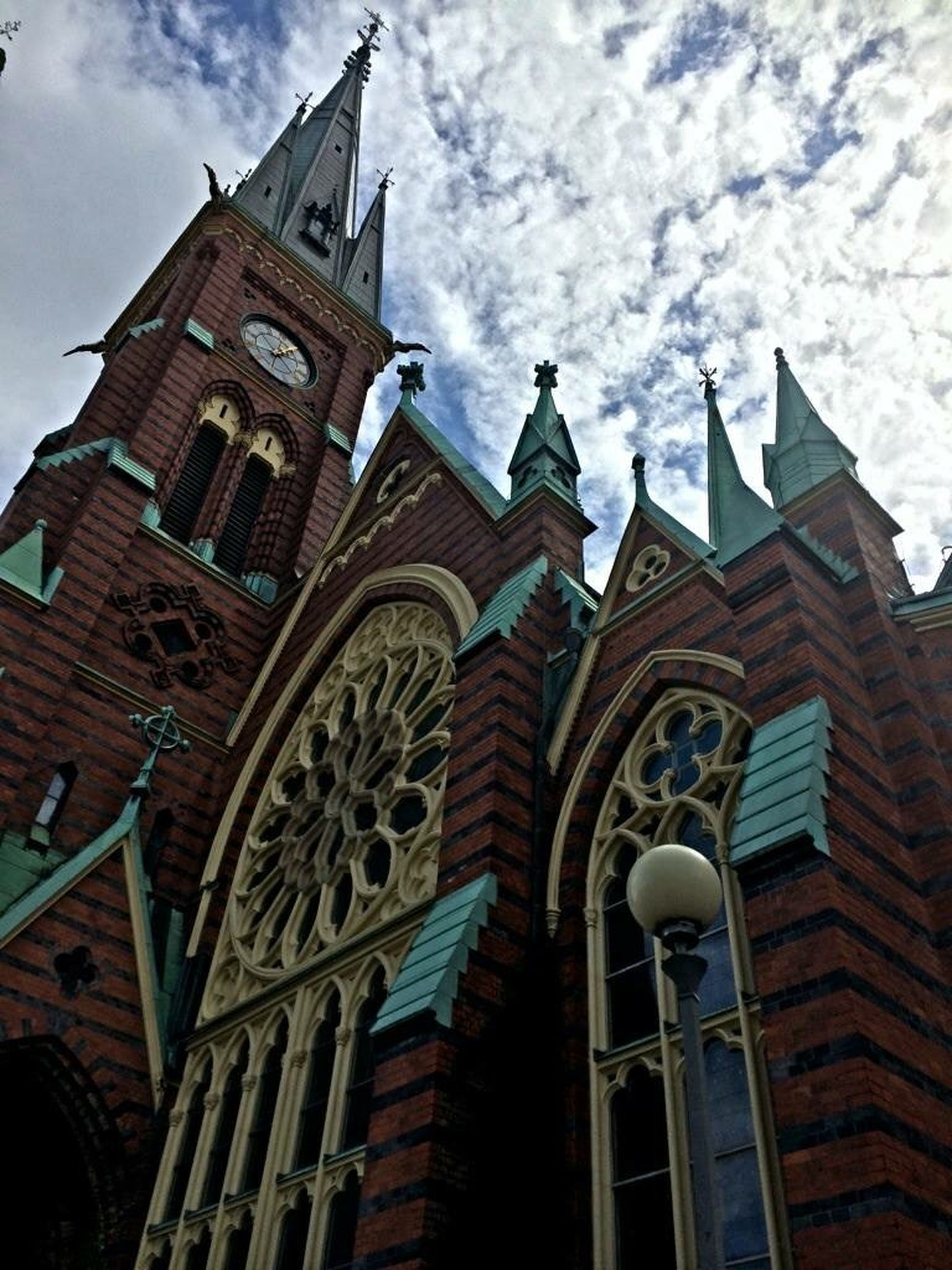 architecture, building exterior, low angle view, built structure, sky, church, religion, cloud - sky, place of worship, window, cloud, spirituality, cloudy, day, outdoors, facade, high section, building