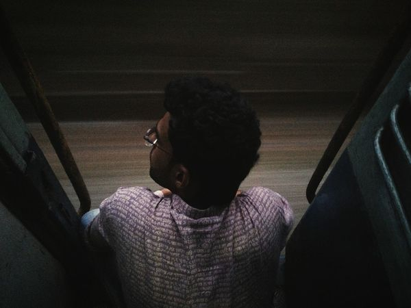Thought filled journey. Boy Man Back View Backside View From Back Sitting Sitting Near Door Looking Out Thinking Thoughts Thoughtful Poetic Moody Grainy Film Dark darkness and light Indian Travel Train Journey Train Journey One Person Lonely Alone Time Single Close-up Thoughtful Asian Ethnicity Shadow