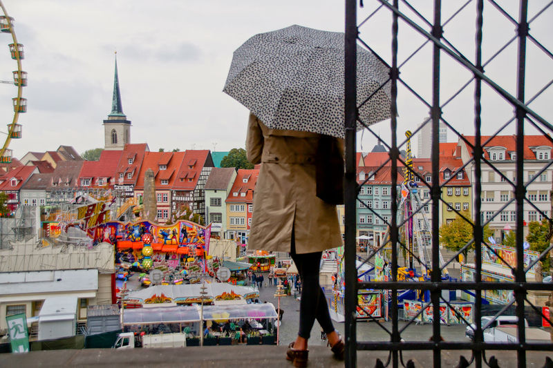 Rear View Of Woman With Umbrella By Gate In City