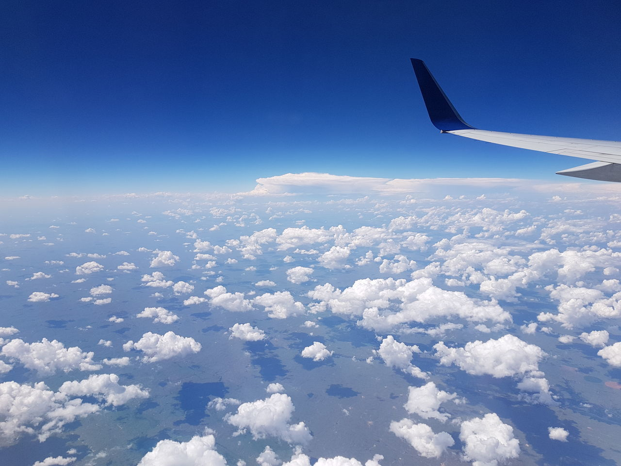 AERIAL VIEW OF AIRCRAFT WING OVER CLOUDS