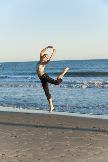 young attractive single woman tourist in spain Balance Beach Beauty In Nature Clear Sky Exercising Flexibility Full Length Healthy Lifestyle Horizon Over Water Leisure Activity Lifestyles Nature One Person Practicing Real People Sand Scenics Sea Sky Stretching Water Wellbeing Yoga Young Adult Young Women