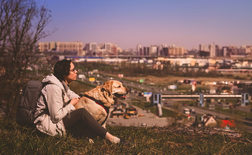 A girl sits hugging a labrador retriever on a mountain against the background of the city