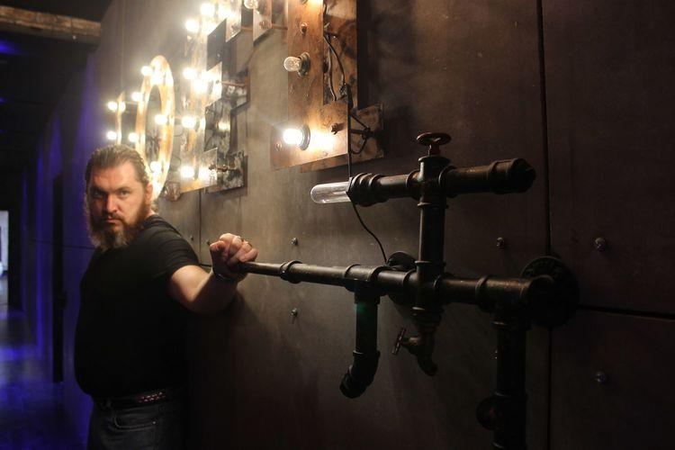 Man standing against illuminated wall