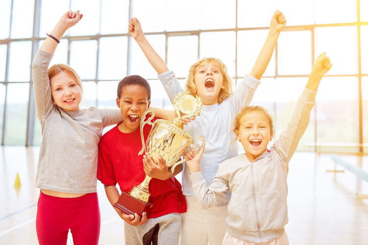 Portrait of happy children standing with trophy