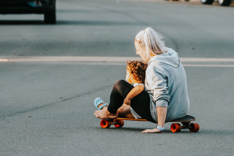Little girl riding on a skateboard with her mum, play time outdoors in suburban street