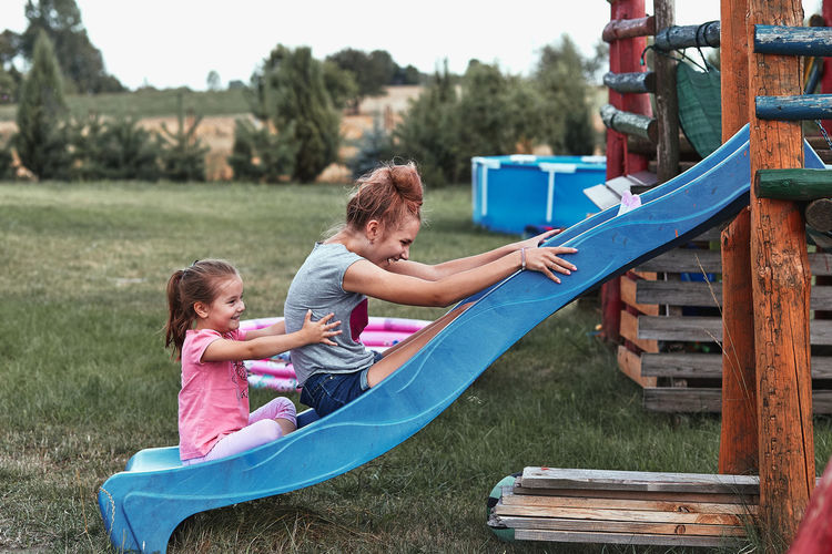 Sisters playing on slide in playground