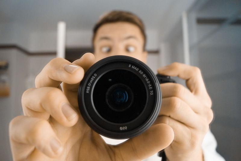Portrait of surprised man holding camera