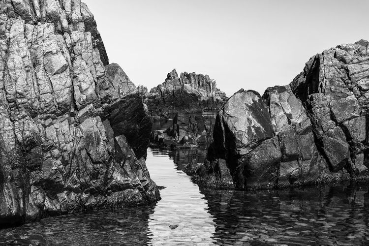 Rock formations by sea against clear sky