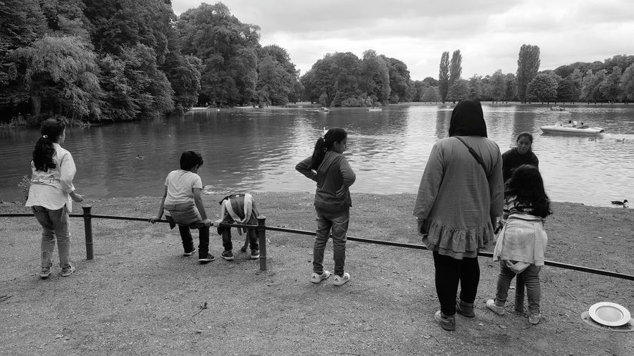 Rear view of people standing by lake against sky