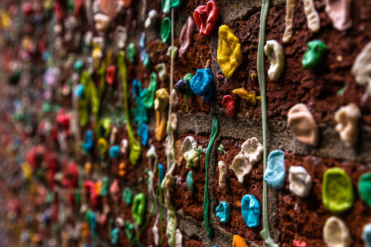 Close-up of bubble gums stuck on brick wall