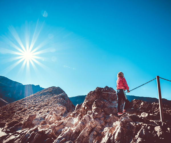 Adventure Beauty In Nature Blue Clear Sky Day Full Length Leisure Activity Lifestyles Mountain Nature One Person Outdoors People Real People Rear View Rock - Object Sky Sunlight Women
