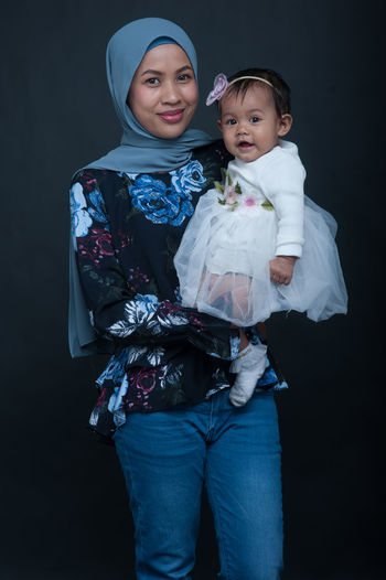 Happy girl standing against black background