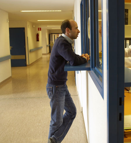 Casual Clothing Indoors  Jeans Real People Standing Young Adult Corridor Asking Information Admission Counter Desk Side View Belgium Medical Hospital Reception Registration Indoors  Man