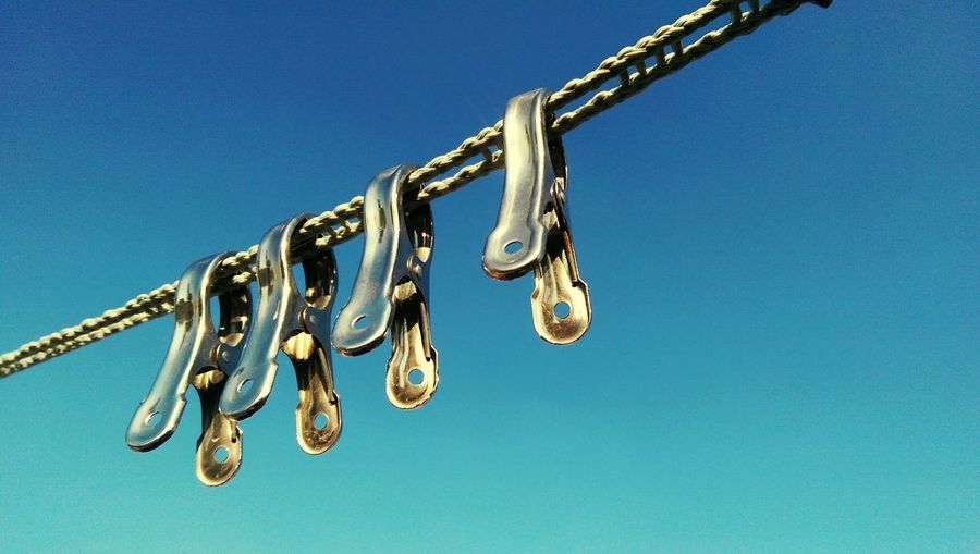 Low Angle View Of Metal Clips Hanging On Rope
