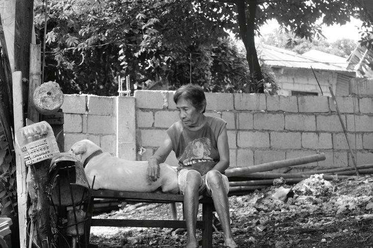 Senior Woman Sitting By Dog In Back Yard