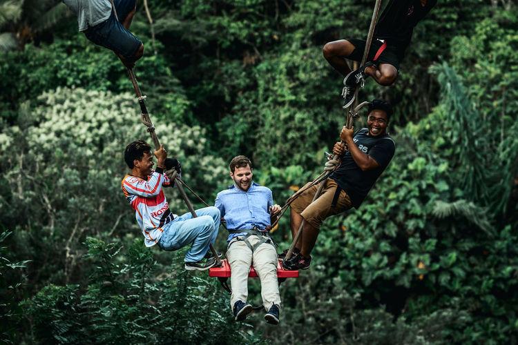 Full length of men on swing in forest