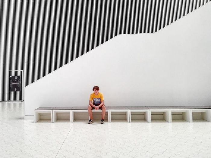 Full length of teenage boy on seat at szczecin philharmonic