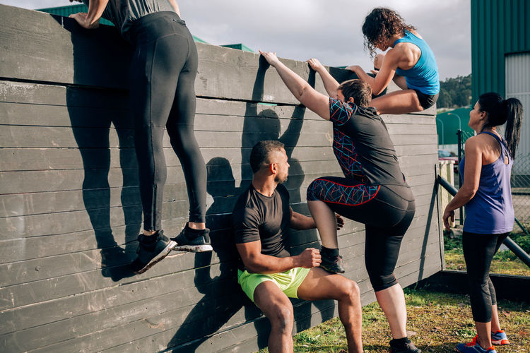 Group of participants in an obstacle course climbing a wall Obstacle Race Obstacle Course Ocr Collaboration Cooperation Runner Sport Exercise Horizontal Extreme Sports Outdoors Competition Athletic Training Workout Strong Boot Camp Effort Power Determination Climbing Wall Team Woman Man Helping