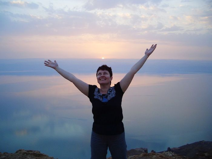 Woman With Arms Raised Standing Against Sea And Sky During Sunset