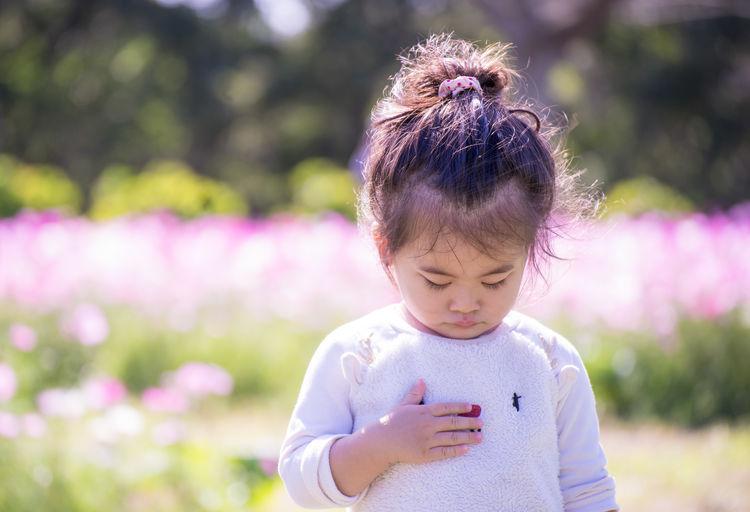 Cute girl holding dandelion against blurred background