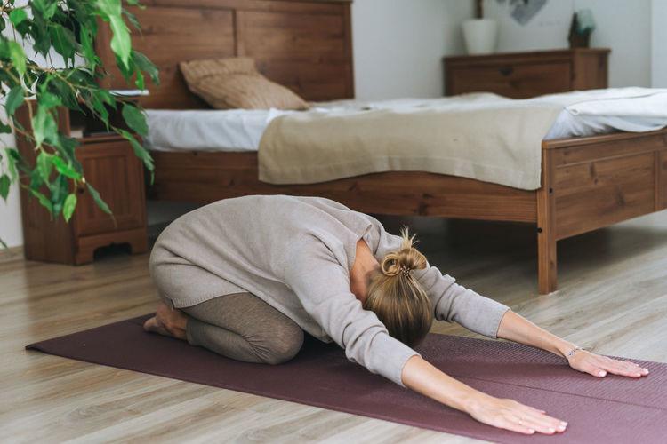Woman lying down on hardwood floor at home