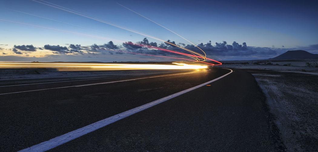 Light trails on road against sky