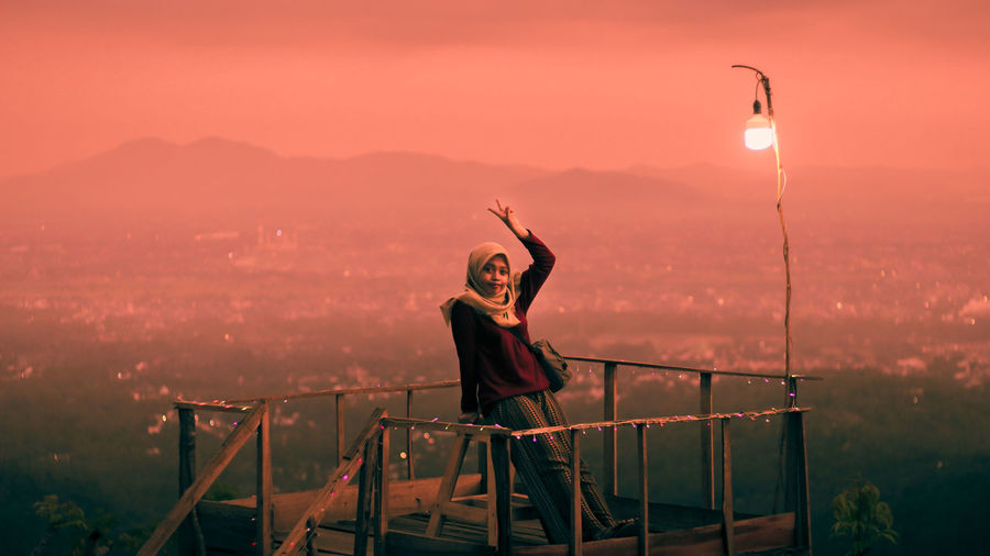 Woman sitting on rooftop by railing against sky during sunset