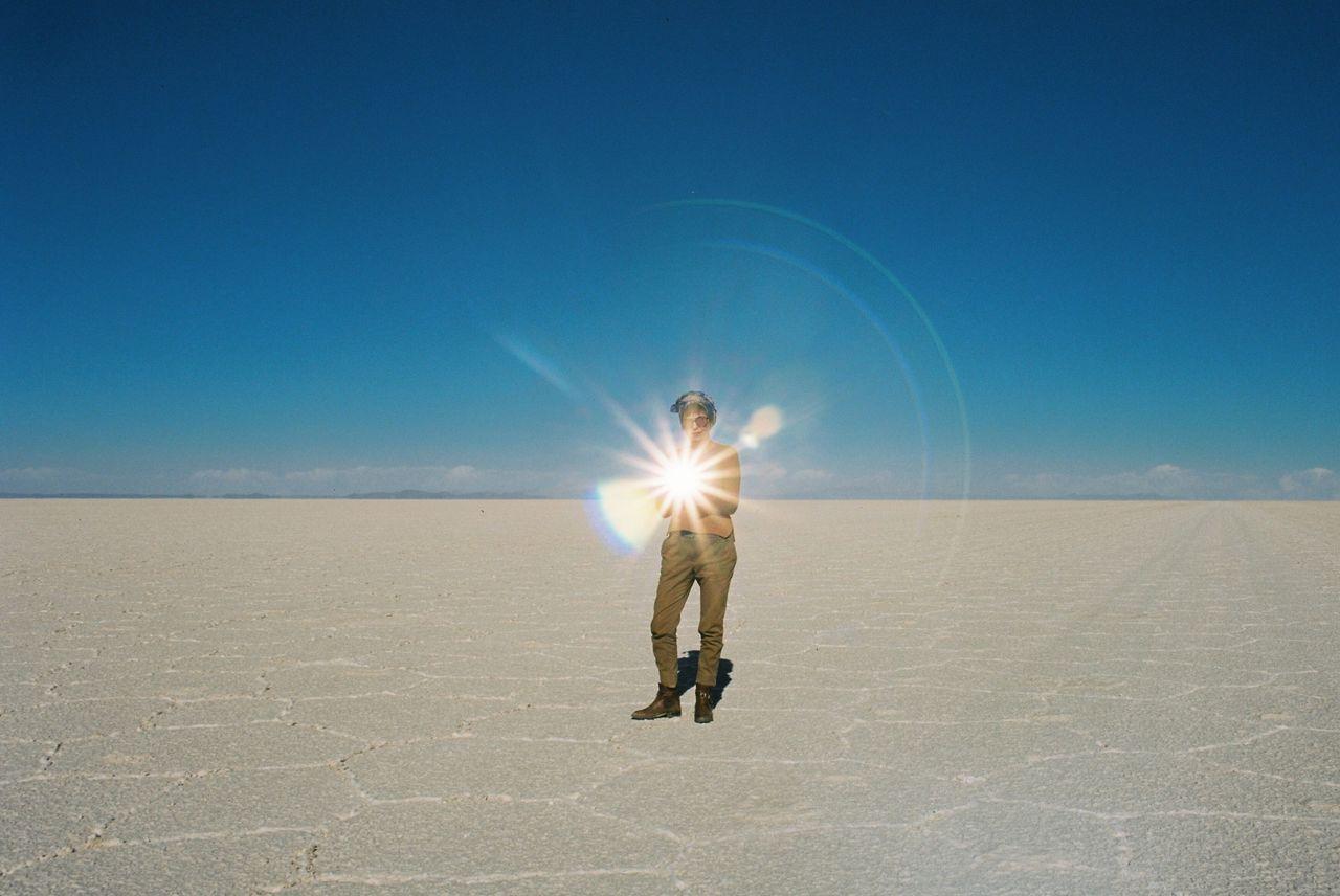 Man standing on salt flat against clear blue sky