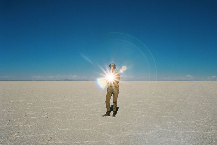 Man Standing On Salt Flat Against Clear Blue Sky